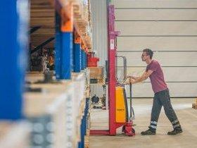Pracownik magazynu wyciąga pompę hydrauliczną dla klienta